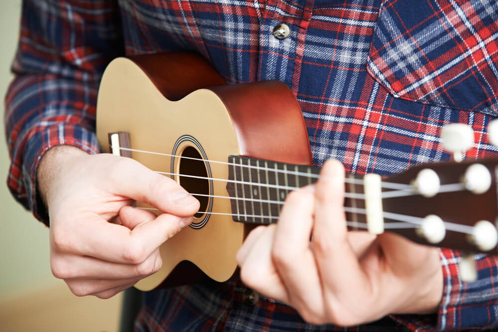 close up of a man playing ukulele